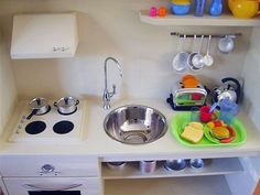 """Homegrown or store bought, play kitchens are a perennial favorite for the preschool set and beyond. They are big winners in the """"big present"""" category, but what's the best way to stock one for your child to enjoy? Here are a few things to consider."""