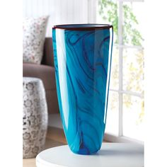 he swirling of a restless ocean is echoed in the rich azure hues of this glass art vase. Captivating like the sea itself, this piece is as fanciful as it functional an ideal vessel to display a vivid