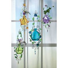 Pastel glass bottles are suspended by metal tendrils decorated in bright, acrylic beads, flowers and leaves. These Pastel Glass Rooters hold cuttings or bouquets and double as unique suncatchers. Wipe clean. Set of 4; one of each - purple, yellow, blue and green. Approx. 13½l.