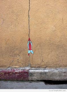 SpiderMan grippe grâce à une fissure dans un mur.