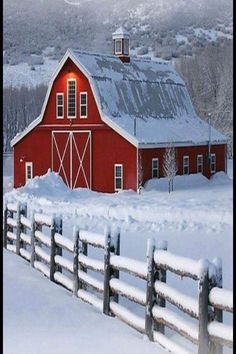 Bright red barn in winter with snow in breathtaking setting. Winter and holiday inspiration.