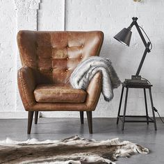 The leather Tobin chair is perfect for that spare corner or a great reading nook, with a winged button back, small tapered arms and dark wooden legs.