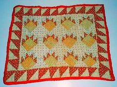 ANTIQUE DOLL QUILT WITH PAW PRINT PATTERN AND RED BORDER.
