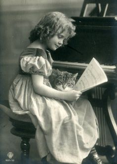 Vintage photo of girl at piano with a cat in her lap