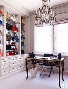 The closet includes an antique desk and open shelving that displays a collection of handbags | http://archdigest.com