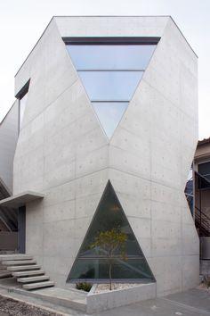 下の開口は1階と地下の半分に、上の開口は2階と3階に面する。 前庭にはブラシノキが植わる。japan-architects.com
