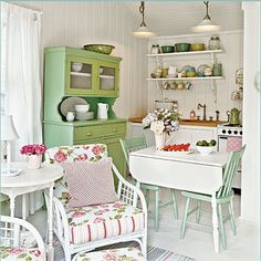 Love the mint green chairs with the white table and the rose-patterned cushions.