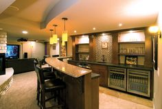 This basement bar provides plenty of space for entertaining. The warm materials and lighting make the space feel welcoming and comfortable.