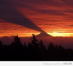 a mountain casting a shadow on the sky. pretty cool.