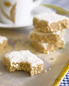 Easy no-bake lemon coconut slice. A biscuit coconut base with tangy lemon icing. No Bake Lemon Slice, Lemon Coconut Slice, No Bake Slices, Good Food, Yummy Food, Yummy Eats, Yummy Snacks, Baking Tins, Sans Gluten