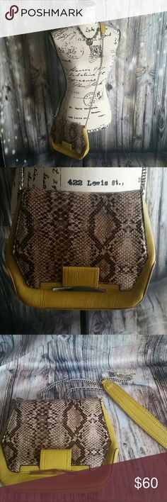 """NWOT, Danielle Nicole faux snakeskin cross body Small bag, 8"""" tall, 9.5"""" across at widest point, and 2"""" deep, button flap closure  and zip pocket on inside. Silver color chain strap and hardware. Chain  has mustard yellow faux leather shoulder strap. Purse hangs aprox 23"""" from the shoulder. Made form 100% polyester materials. Danielle Nicole Bags Crossbody Bags"""
