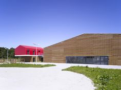 Modern equestrian facility, Bois d'Arcy. Riding arena with timber finish and a clubhouse clad in red.