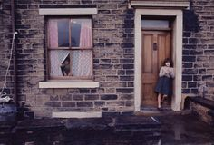 A girl stands in a doorway, Manchester, England, United Kingdom, photograph by John Bulmer. Color Photography, Vintage Photography, Street Photography, Portrait Photography, Urban Photography, Martin Parr, Street Portrait, Girl Standing, First Photograph