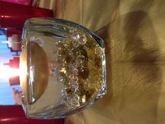Floating candle centerpiece. Small, square glass bowl filled across the bottom with gold marbles and plastic diamonds, fill with water and add a floating candle! Simple and pretty!! I used this at my parents 50th wedding anniversary! Found everything at Garden Ridge.