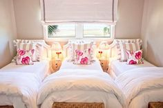 Who would have thought that three beds could be wedged into such a small room?  I love the punch of pink on the pillows and the woven trunks.