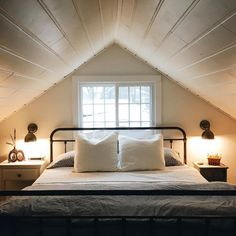You would have to mind your head when getting up in the morning but I dearly love what I see in this charming attic bedroom. The ticking duv...