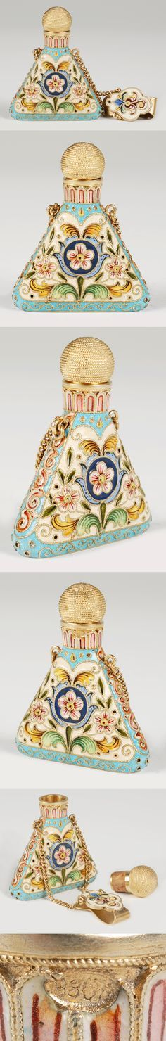 Fabergé scent bottle | A Russian silver gilt and cloisonne enamel scent bottle, Feodor Ruckert, Moscow, circa 1896-1908. Of triangular form with replacement, pull-out, cork-mounted stopper, the body decorated with scrolling floral and foliate motifs against a cream ground within a turquoise border, the clip similarly decorated.