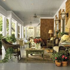 """Great porch with beadboard ceiling in """"haint"""" blue, ceiling fans, cedar shakes and copper gas lanterns"""
