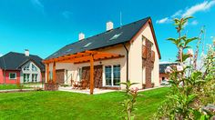 Dům Uno má klasickou sedlovou střechu, fasádu v krémovém odstínu, která se kombinuje s kamenným obkladem. Příjemná je pergola s posezením a travnatá plocha.
