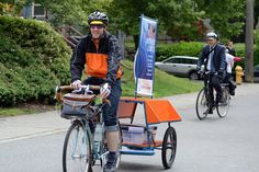 """A librarian on a bicycle tows a cart that can transport up to 500 pounds of books as part of Seattle's """"Books on Bikes"""" summer pilot program. (Seattle Mayor's Office / June 12, 2013)"""
