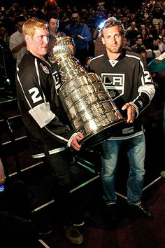 Los Angeles Kings players Matt Greene, left, and Jarret Stoll carry the Stanley Cup into the theater at the premiere of the team's championship DVD.