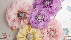 Learn how to make these pretty paper flowers with a special sparkle. Add flutters of colour and texture to your home with gorgeous paper flowers. String them on fishing wire, secure with pins to fabric or curtains; you could even add them to your clothing as a brooch. Look for unique coloured paper and textures for amazing results. ~What you will need: Tissue paper Glue Scissors Rings (we used Swarovski 'chic pink' ring [pink stones]; Peeptoe enamel ring [square]; Peeptoe Swarovski crystal…