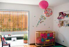 Revestidas com tecidos estampados, as luminárias de teto redondas ficam sobre o berço no quarto do bebê
