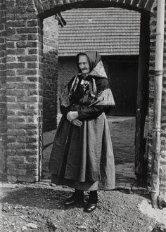 Vrouw in zondagse- en feestdracht, Stein. Zij draagt een wit mutsje, met daarover een 'kopplak' (hoofddoek), een 'schouderplak' (schouderdoek), 'teertese rok', paars zijden schort, zwarte kousen, zwarte schoenen en een gouden borstplaat met kruisje. 1952 #Limburg #Stein