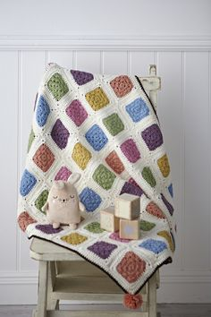 crochet cot blanket on against white t&g on white wooden floor