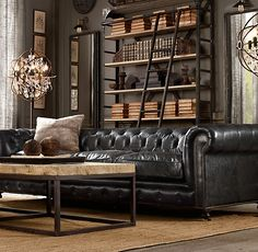 Dramatic & masculine with a leather tufted sofa, shelving with rolling ladder and 2 'ultra tech' floor lights. Industrial chic with a lavish taste.