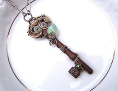 """Opalite Swarovski Wire Wrapped Antique Skeleton by FawneyFortune: This antique steel skeleton key is wire wrapped with antiqued silver wire and adorned with three iridescent, prismatic Swarovski crystals and a blue-green opalite Swarovski heart. Additionally, the top of the key is decorated with a hand shaped and hammered swirl to create a one of a kind bail. The pendant is hung from an antiqued silver 23"""" chain, which should be long enough to slip over one's head."""