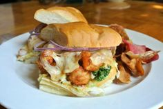 Menu Item: Shrimp & Langoustine Po' Boy with tempura battered shrimp and fresh langoustine, deep fried on a sourdough roll with kale coleslaw, ghost pepper jack cheese & chipotle remoulade, served with crispy root vegetable chips.