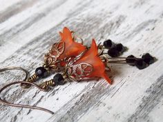 """These fabulous flower earrings are composed with lucite bell flowers, antique brass and Swarovski Crystals. These are sure to make a Boo-tiful compliment to your attire. Measures 2-1/2"""""""
