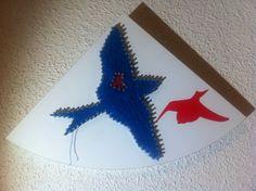 Cuadro de golondrinas hecho con un tablón de madera, clabos, hilos de colores y una pegarina