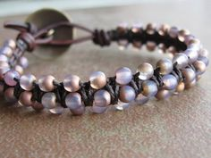 Smooth, round Czech glass beads in a soft, milky pink shade with a matte gold finish were woven onto naturally-dyed antique brown leather cord