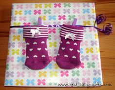 Baby shower gift wrap idea: attach a pair of baby socks hanging on a clothes line
