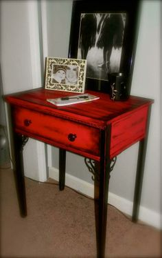 A lot of sanding, wood glue, wood filler, added reinforcements on legs with iron scrolls, and decorative knobs. This cute distressed accent table is painted deep red and black.
