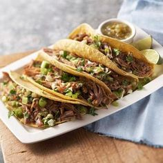 Mexican Tacos Carnitas - Slow-cook pork shoulder roast and Mexican spices to tender goodness, then serve with corn tortillas. Fresh cilantro, green onion and bottled green salsa add the finishing touches.