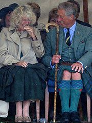 Prince Charles trying to keep his kilt under control, cracking Camilla up