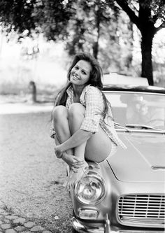 What is the old sportscar she is perched upon?