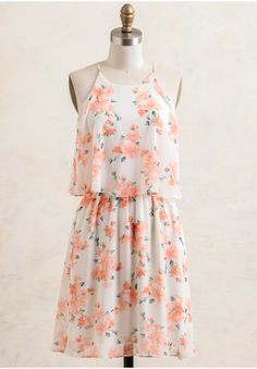 Effortless and flowy, this white chiffon dress is beautifully decorated with a peach-hued floral print and designed with a tiered bodice.
