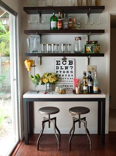 Gorgeous dining room features a steel and marble table turned bar area topped with a wooden bar ...