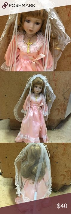 Bride porcelain doll This porcelain doll has strawberry blond hair with brown eyes she has a cross around her neck she's wearing a veil she's in perfect condition her shoes and socks are there she comes with a stand and her dress is a peach apricot color Other