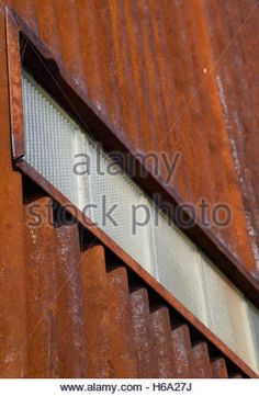 Old, Rusty, Corrugated Metal Wall with Row of Glass Brick Photographed at an Angle from below - Stock Photo