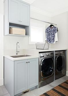 Gray transitional laundry room features pale gray cabinets adorning polished nickel knobs and fitted with a stainless steel sink paired with a polished nickel gooseneck faucet mounted to a white quartz countertop.