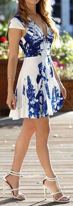 Vestido blanco con estampado en azul fuerte y tacones abiertos blancos.