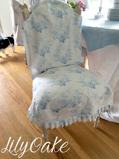 """Lilyoake's """"Blue Roses Wreath"""" pattern on linen cotton canvas, shown as a chair slipcover. Available on Spoonflower in 17 different fabrics, 2 types wallpaper and gift wrap!"""