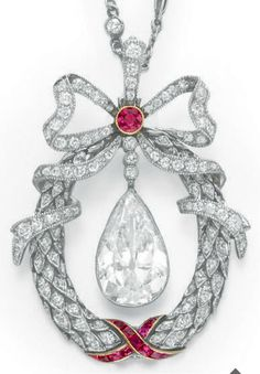 A BELLE ÉPOQUE DIAMOND AND RUBY PENDANT NECKLACE. Suspending a pear-shaped diamond, weighing approximately 3.76 carats, within a single-cut diamond foliate wreath, decorated with calibré-cut ruby ribbon detail, topped with a single-cut diamond bow, centring upon a collet-set ruby, from the fine link platinum neckchain, spaced by collet-set diamonds, mounted in platinum and gold <3