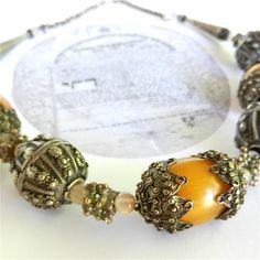 Carefully restored bridal dowry style necklace with bakelite faturan amber beads capped with the intricate silver granules and strung with signed starburst design oxidized silver beads.  Three of the