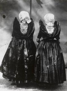 Twee meisjes in Axelse streekdracht. Het linker meisje draagt over de ondermuts en het oorijzer een 'trekmuts'. Het rechter meisje draagt de 'ronde muts' of 'hernhuttermuts'. Beiden zijn gekleed in zondagse dracht.  De opname is gemaakt in 1913 te Amsterdam, tijdens het Klederdrachtenfeest. Dit was onderdeel van de festiviteiten rond de 100-jarige onafhankelijkheid van Nederland (1813-1913). #Axel
